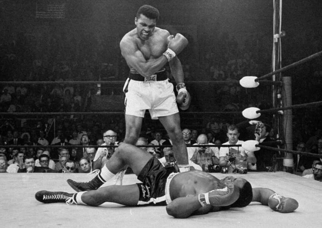 Heavyweight champion Muhammad Ali stands over fallen challenger Sonny Liston shortly after dropping him with a short hard right to the jaw in Lewiston on May 25, 1965.