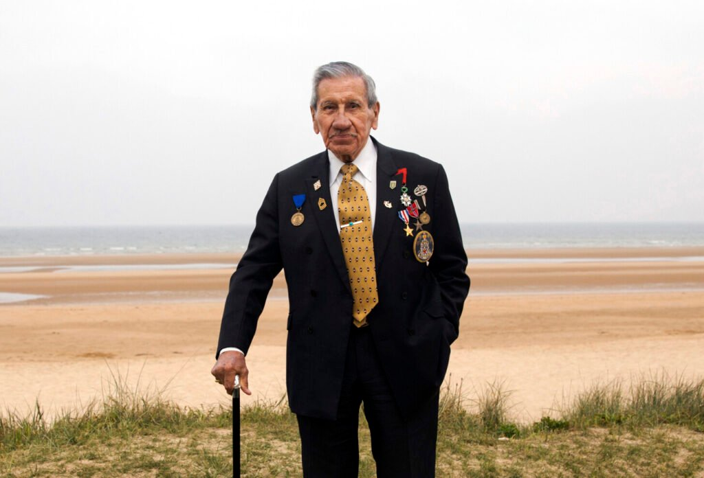 Charles Norman Shay poses on a dune at Omaha Beach in Saint-Laurent-sur-Mer, Normandy, France on May 1, 2019.