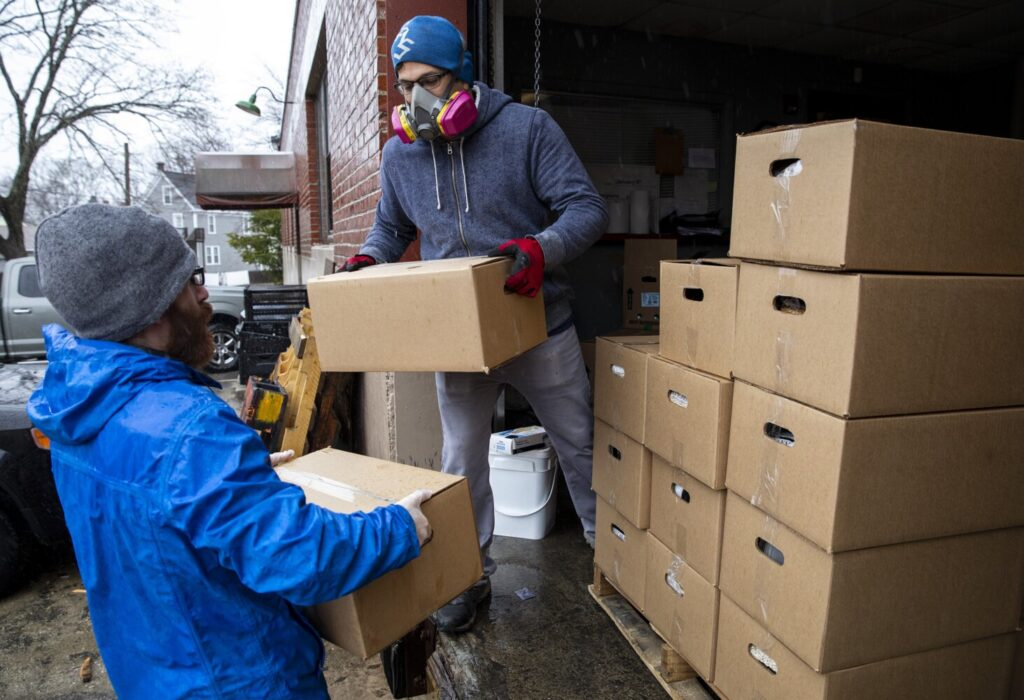Nick DeSouza hands Portland Public Schools employee Nick McRae boxes filled with food  for families in need at Wayside Food Pantry on Friday. McRae loaded up his car with boxes and then drove them to Casco Bay Lines to be put out on to the ferry for island families. Portland Public Schools started doing a supplemental food drop for dozens of vulnerable families. The district reached out to Wayside Food Pantry to see if they could help. The food pantry usually does 60 to 80 food boxes a week and are now doing about 500 boxes a week. (Staff photo by Brianna Soukup/Staff Photographer)
