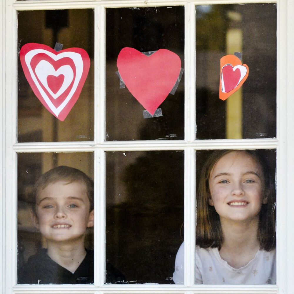 Callan Grant, 7, left, and Libby Grant, 11 stand for a portrait in front of the hearts they made on Saturday at their Augusta home.