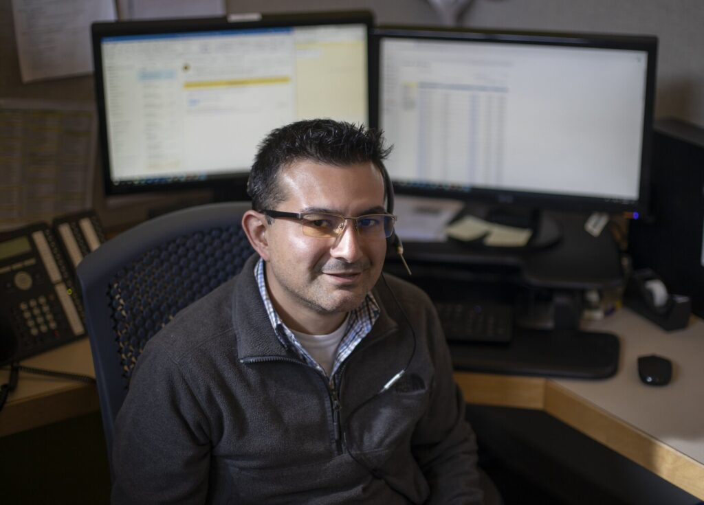 Michael Perez, 34, a senior at the University of Southern Maine, works as a 211 call operator in South Portland. The coronavirus pandemic has reshaped his role. Now, he and other specialists offer callers information such as CDC health guidelines or refer them to the best resources.
