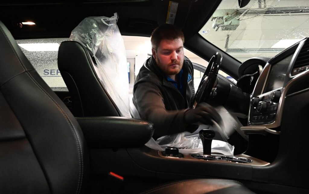 Sam Berry, a service advisor with Lee Auto Mall in Westbrook, cleans the interior of a vehicle after it was dropped off for service Monday. Car dealers in Maine are promoting repair and maintenance service while offering deals on car sales by phone or over the internet.