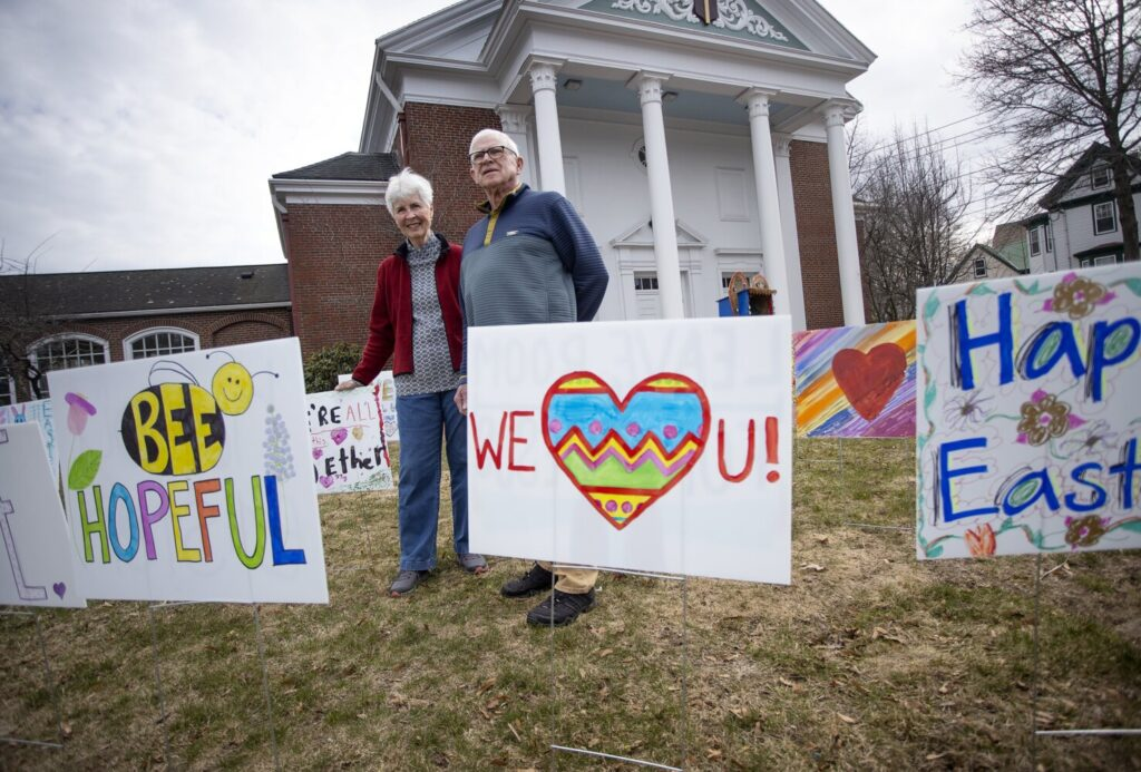 Volunteers Robin and Bill Carter will put out signs created by children on the front lawn of Woodfords Congregational Church on Saturday afternoon. The congregation will celebrate a sunrise service via Zoom on Easter morning.