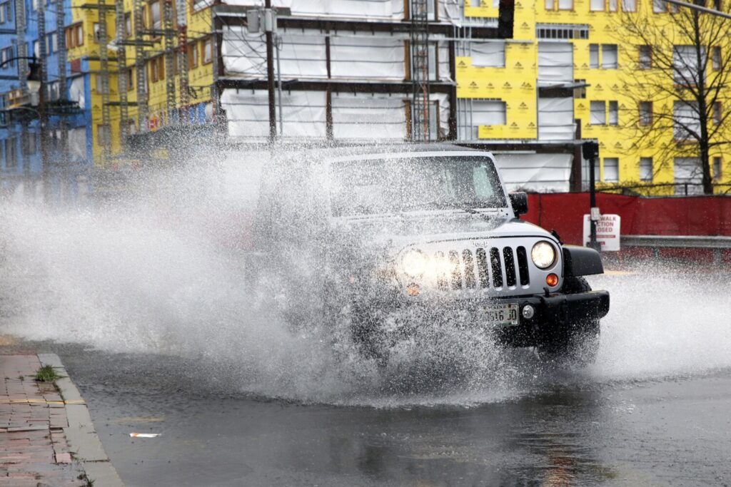 A Jeep blasts through a deep puddle at the intersection of York and High streets in Portland on Monday.