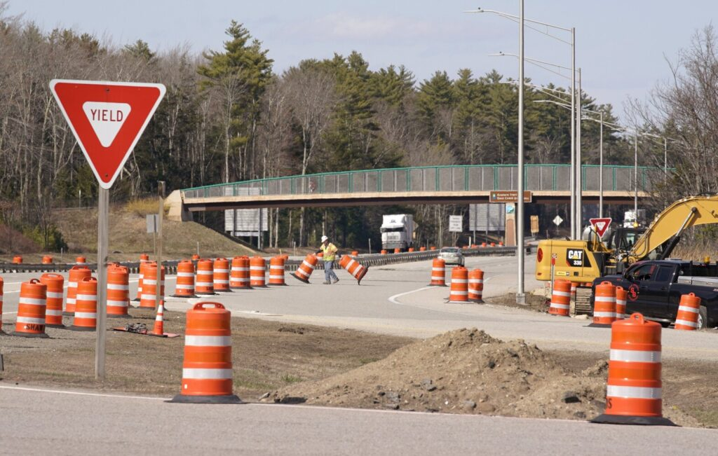 A construction worker with Shaw Brothers pulls barrier barrels across the on-ramp at the northbound Maine Turnpike service plaza in Kennebunk on Tuesday. Because of a sharp drop in traffic, road construction projects throughout the state are moving along faster than scheduled.