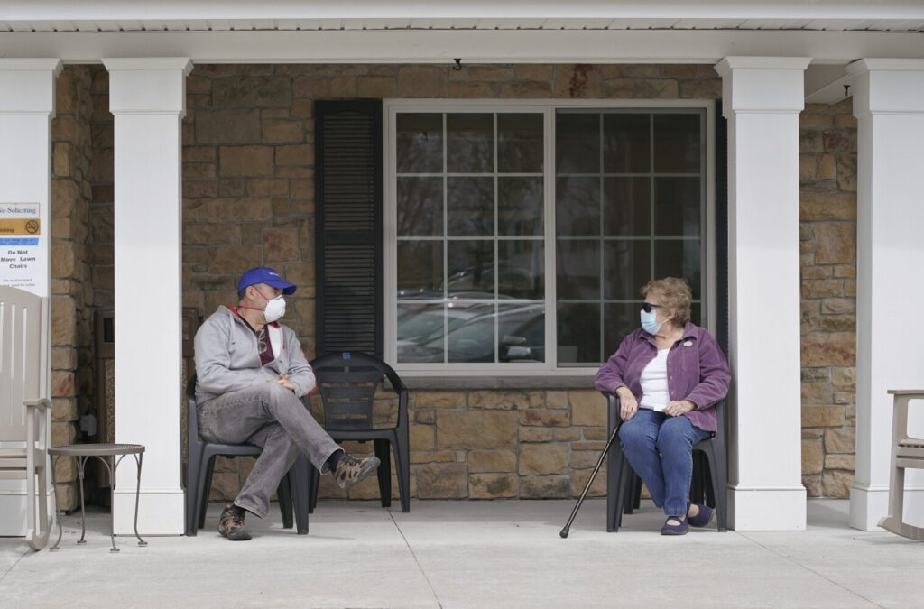 Michael Archibald of Portland visits with his mother, Annie Archibald, on Monday outside The Enclave of Scarborough, where she lives. She hasn't left the senior living community in weeks, as her social life has been shut down.