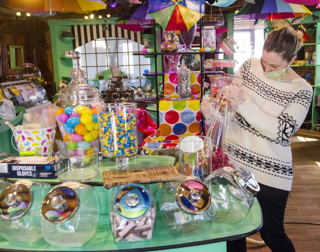Scrummy Afters Candy Shoppe co-owner Hilary Vellani pours candy into a bag Thursday at the store in Hallowell. The shop at 136 Water St. is closing permanently Friday so the owners can focus on online and mobile sales.