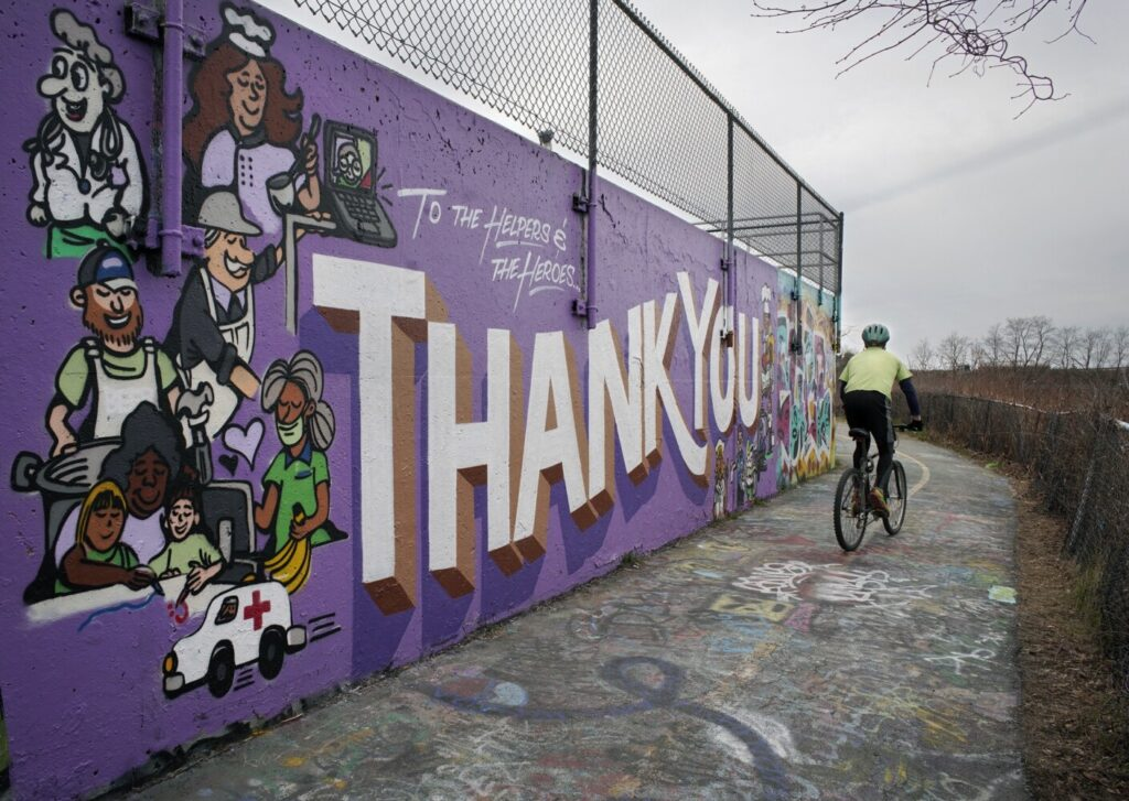 A bicyclist passes by a mural thanking the helpers and the heroes of the coronavirus pandemic on a wall near the wastewater treatment plant in Portland on Friday.