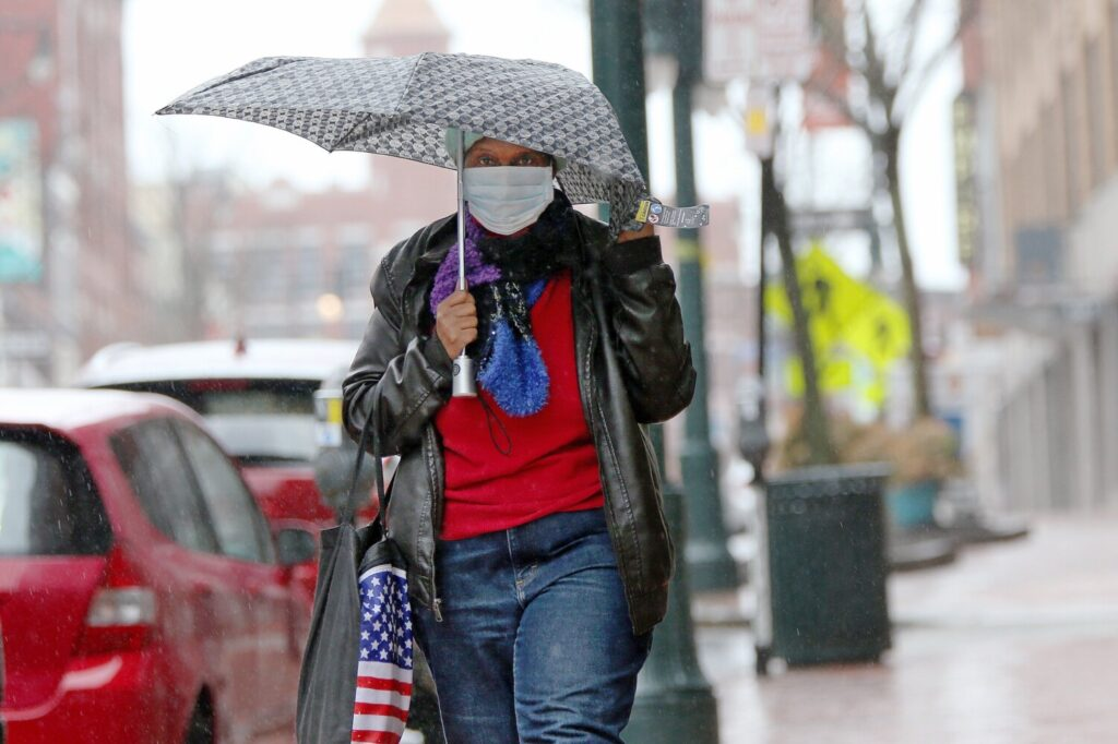 A masked woman clutches an umbrella against rain and wind while walking along Congress Street on Monday.