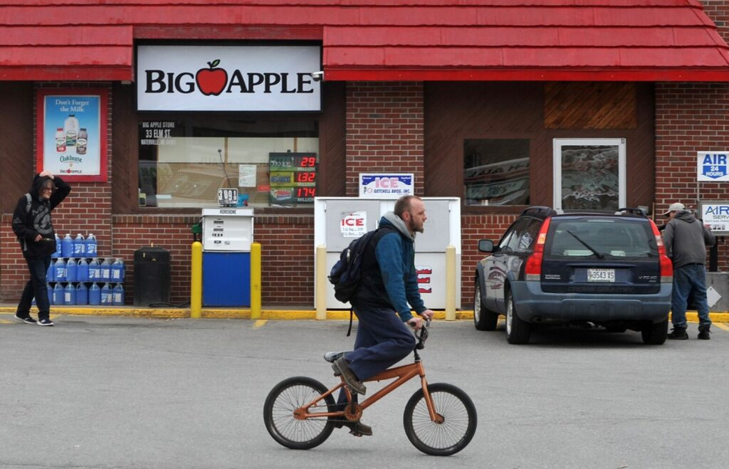 Customers and others Tuesday at the Big Apple Store at 33 Elm St. in Waterville. The store was robbed at knife point early Monday morning.