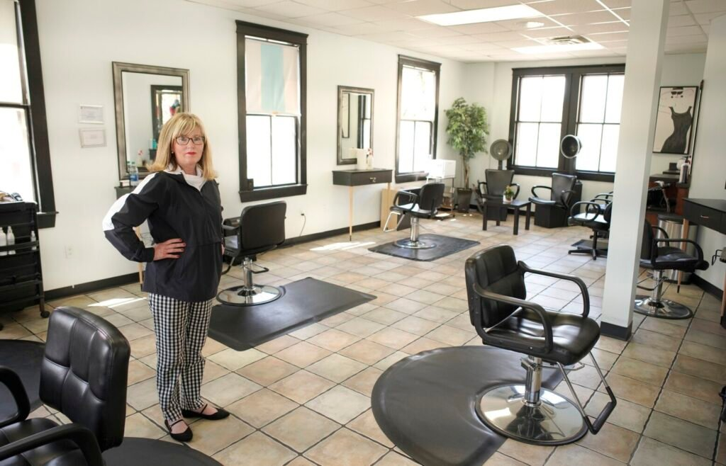 Dani Nisbet, owner of the Belissimo salon in South Portland, stands in the primary salon room Wednesday. Nisbet hopes to open the salon Saturday but is waiting to see operating guidelines from the state. With only four stylists working at a time, Nisbet says she can provide space between customers. She also plans to hang shower curtains around the stylists' chairs to add a layer of protection.