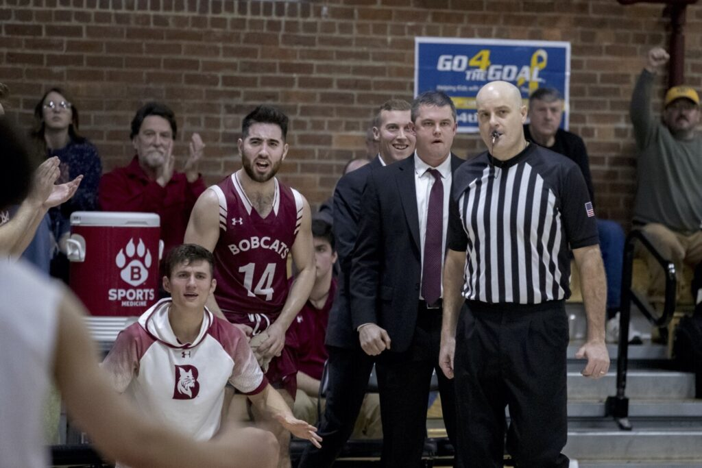 Bates College assistant men's basketball coach Sam Leal stands behind head coach Jon Furbush as they both watch the Bobcats take on Hamilton College in Lewiston last season.