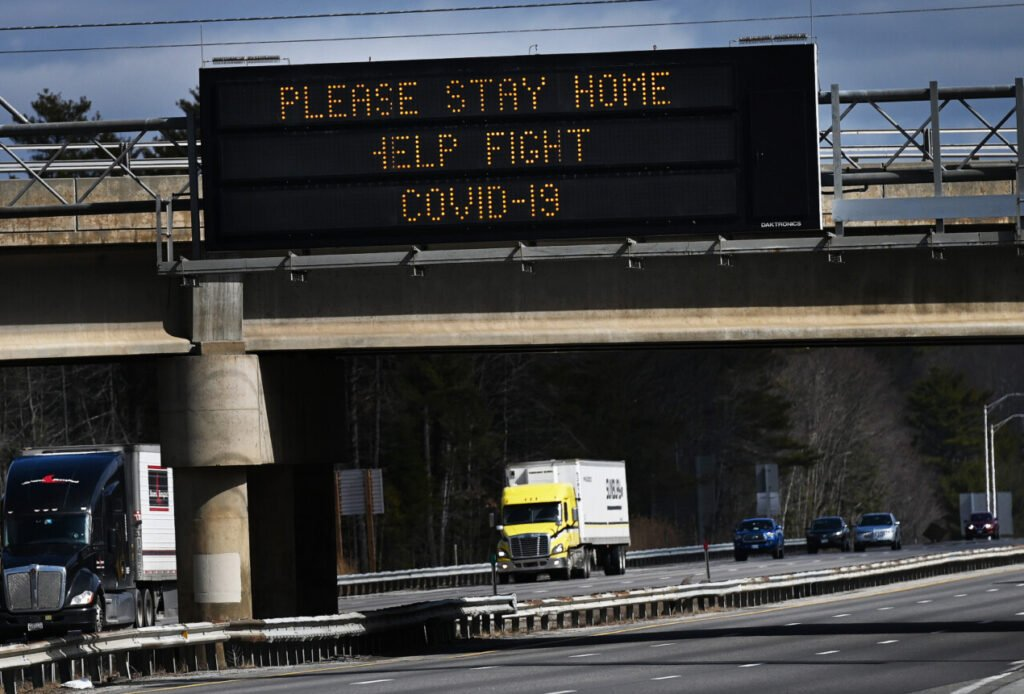 A sign along the Maine Turnpike in Scarborough urges everyone to stay home to help fight COVID-19 on March 31. With fewer cars on the road, some auto insurance providers are starting to offer rate discounts to their customers.