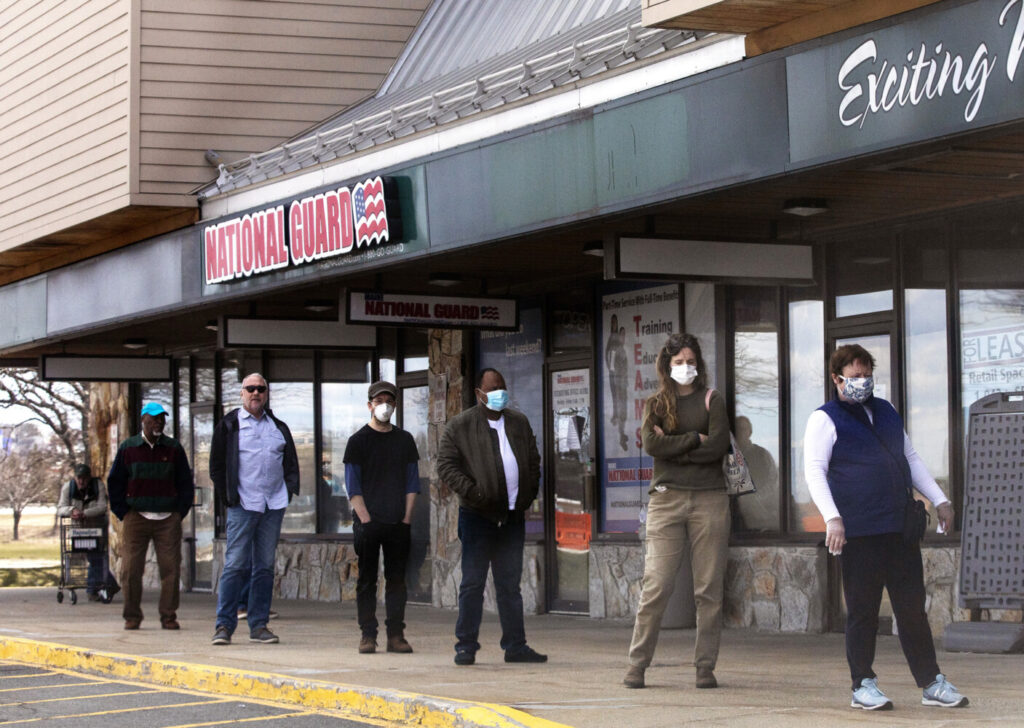 People wait in line six feet apart to go into Hannaford in Portland on Tuesday, April 7.