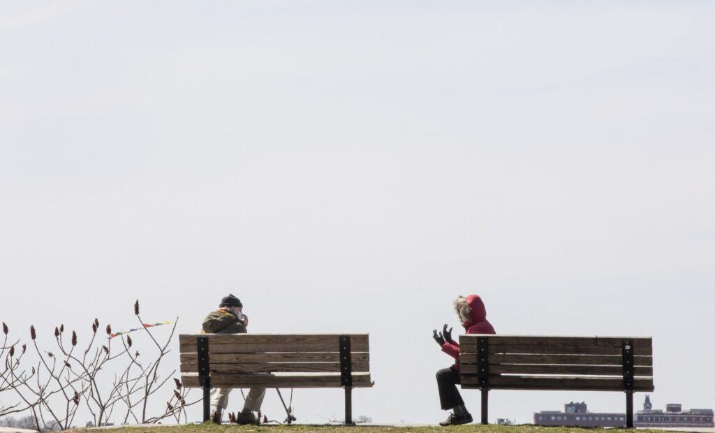 Two people, who declined to give their names, sit six feet apart while taking in the view at Fort Sumner Park on Tuesday.