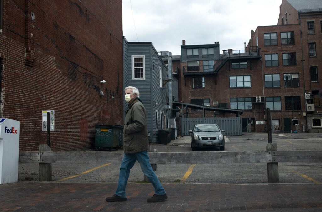 A man wears a mask as he walks down Commercial Street in Portland on Wednesday, April 15.