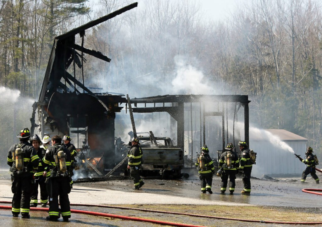 Firefighters douse hot spots Sunday afternoon on Gorham Road in Scarborough where a blaze destroyed a barn.