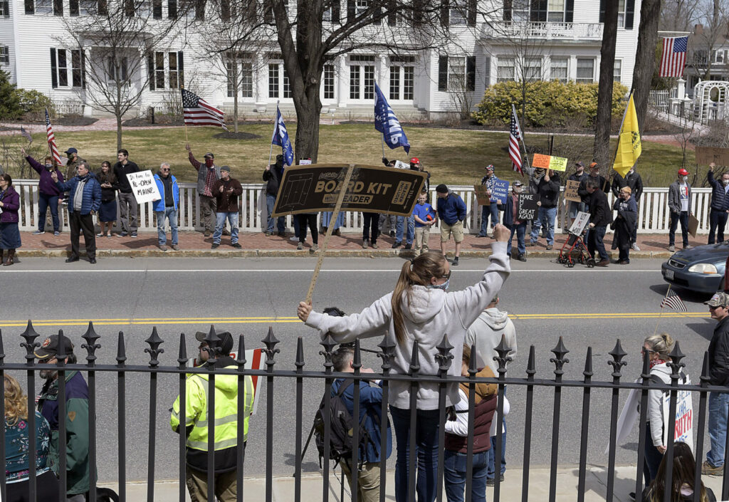 Protesters assemble Monday outside the State House Augusta, where hundreds of people gathered to call for coronavirus restrictions to be lifted. The governor's mansion, called the Blaine House, is seen in the background.