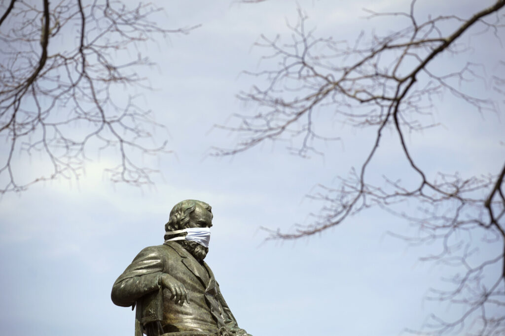 The statue of Henry Wadsworth Longfellow at Longfellow Square in Portland is adorned with a protective mask Monday.