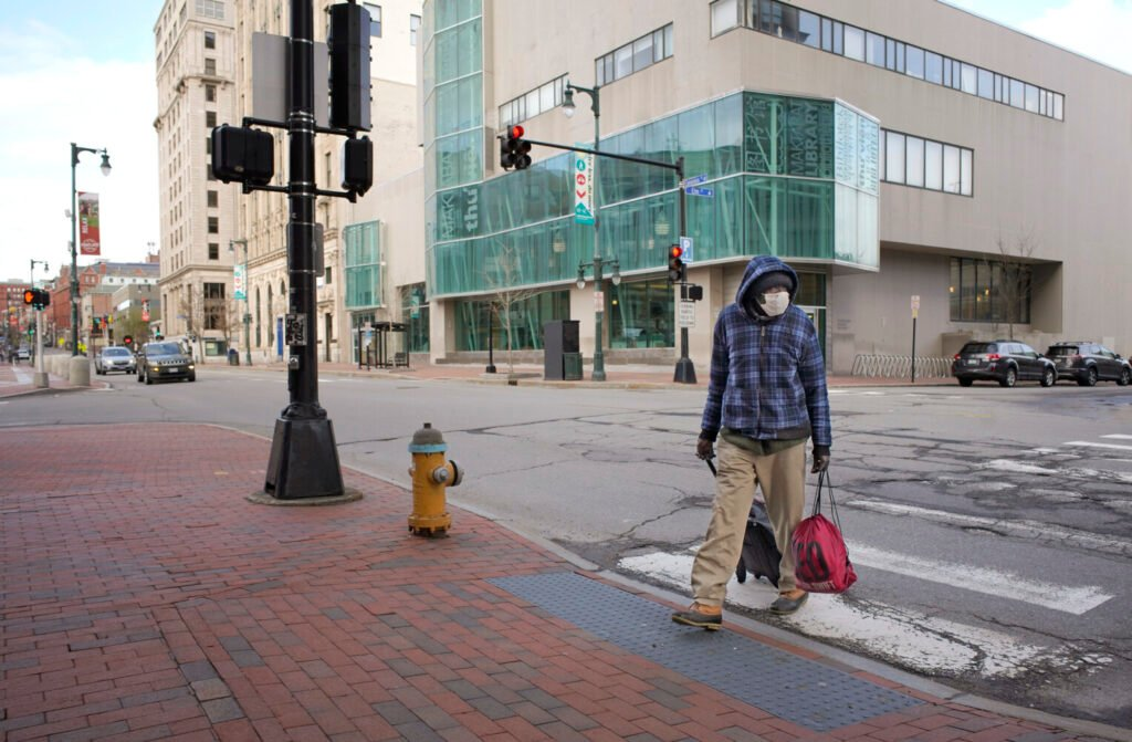 A man crosses a nearly-deserted Congress Street in Portland on Wednesday.