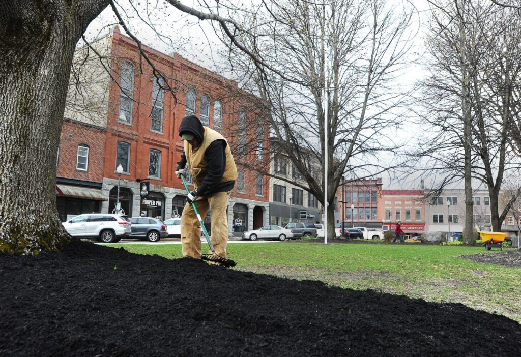 George Kuckenbarker of Waterville Parks and Recreation is dressed for the cold as he rakes black mulch while landscaping with Chad Glidden on Castonguay Square in Waterville on  Tuesday. It has been a cold and blustery month in northern New England, though temperatures could become more seasonal in parts of the states later this week.