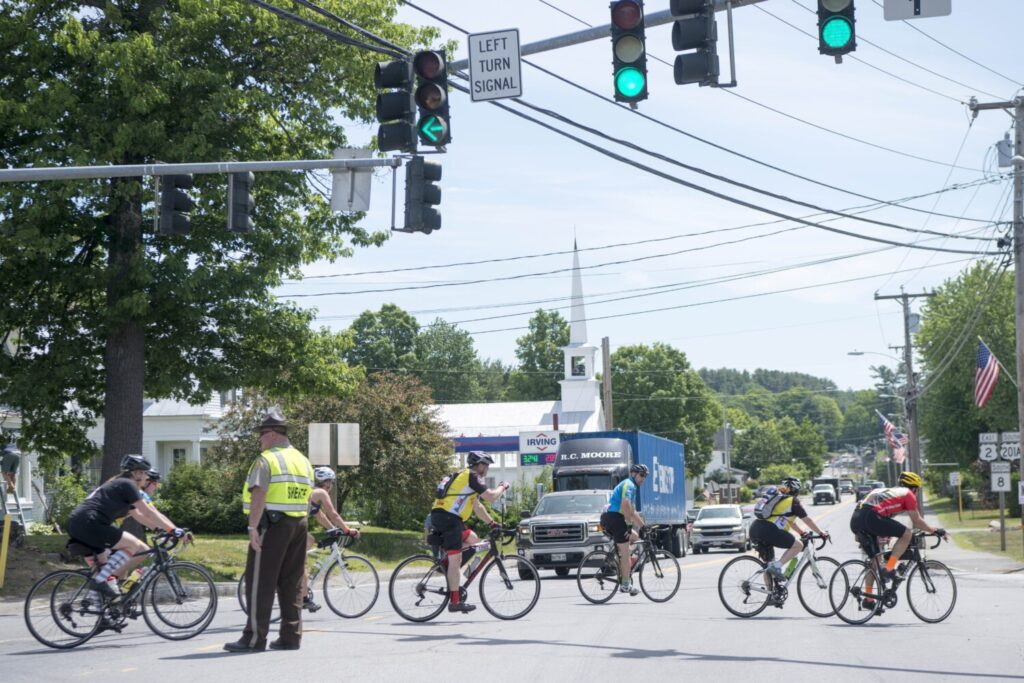 A Somerset Sheriff holds traffic for a massive group of bikers in Norridgewock during the Trek Across Maine ride in 2018.