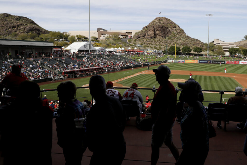 Fans watch a spring training baseball game between the Los Angeles Angels and the San Diego Padres, Thursday in Tempe, Ariz. There have reportedly been discussions between MLB and the players' union about bringing every team to Arizona and starting the season there.