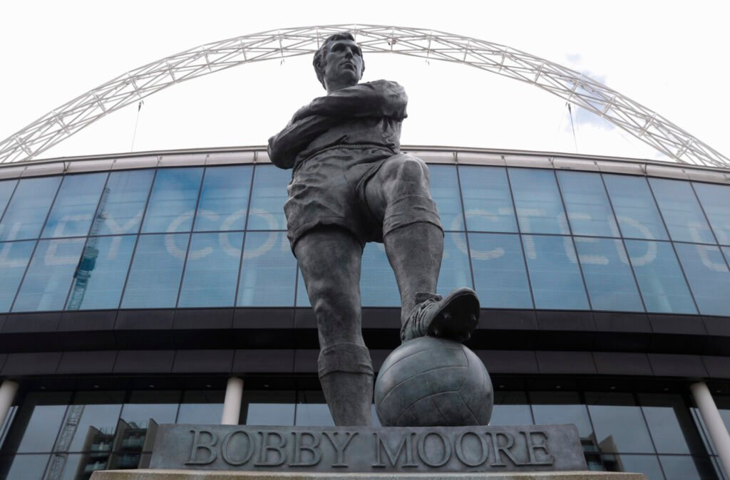 The statue of the late England player Bobby Moore outside Wembley Stadium in London, Tuesday, March 17, 2020. UEFA has formally proposed postponing the 2020 European Championship for one year because of the coronavirus outbreak. The Norwegian soccer association says the new tournament dates will be June 11 to July 11. (AP Photo/Alastair Grant)