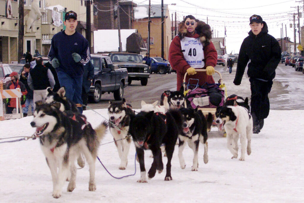 "Emmitt Peters, center, is followed by his sons Emmitt Jr., left, and Emory as he drives his team up the finish chute of the Iditarod Trail Sled Dog Race in Nome, Alaska. Alaska State Troopers confirm Peters, nicknamed the ""Yukon Fox,"" died Thursday, April 2, 2020, at his home in Ruby, Alaska."