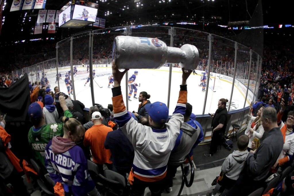 New York Islanders players take the ice as a man holds a makeshift Stanley Cup prior to Game 1 of a first-round playoff series in April 2019. No one knows when or if the NHL will be able to resume play and begin the playoffs.
