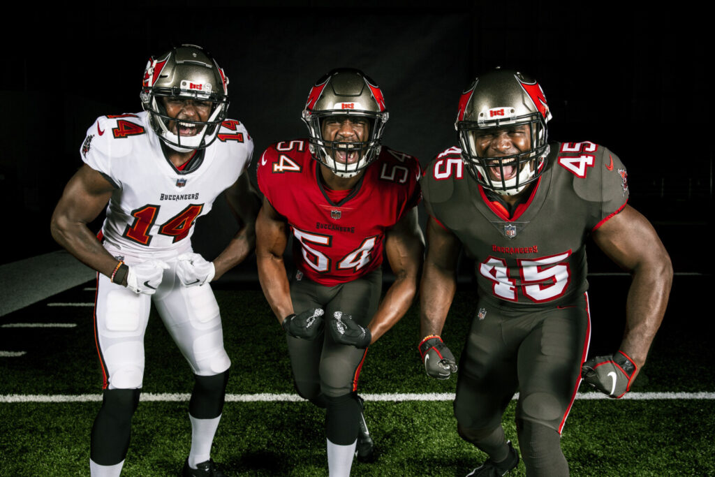 In this handout released by the Tampa Bay Buccaneers, from left, wide receiver Chris Godwin, linebacker Lavonte David, and linebacker Devin White, wear the team's new uniforms.