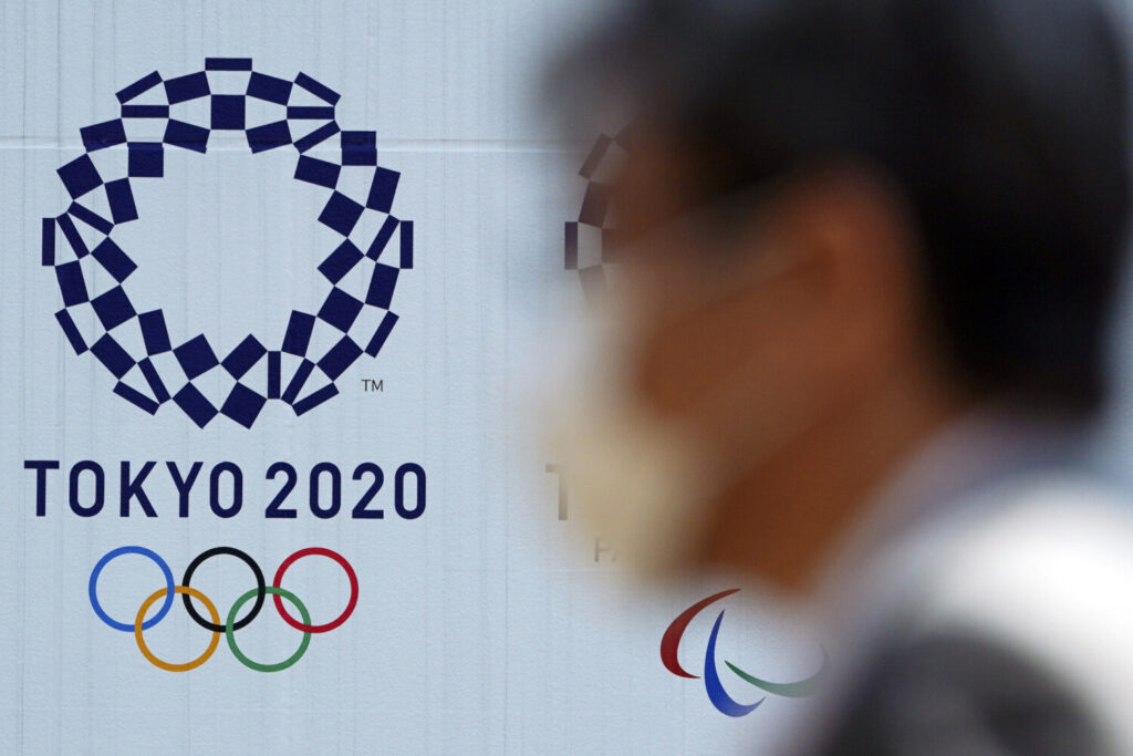 "A man wearing a face mask walks near the logo of the Tokyo 2020 Olympics, in Tokyo. Tokyo Olympic organizers said Tuesday they have no ""B Plan"" for again rescheduling the Olympics, which were postponed until next year by the virus pandemic."