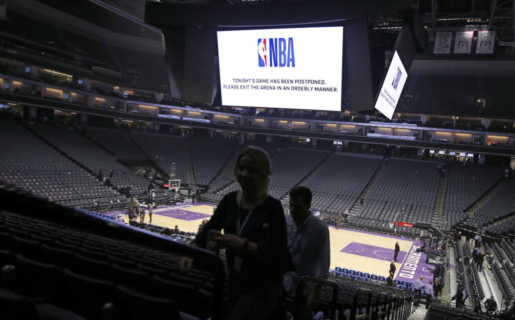 Fans leave the Golden 1 Center  in Sacramento, Calif., after the NBA basketball game between the New Orleans Pelicans and Sacramento Kings was postponed on March 11. NBA facilities will not reopen until May 8, at the earliest, and there will be strict rules when they do.