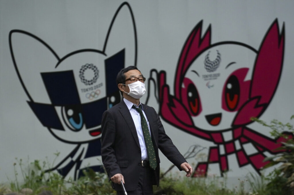 A man with a face mask walks in front of Miraitowa and Someity, mascots for the Tokyo 2020 Olympics and Paralympics at a park in Tokyo on Tuesday.