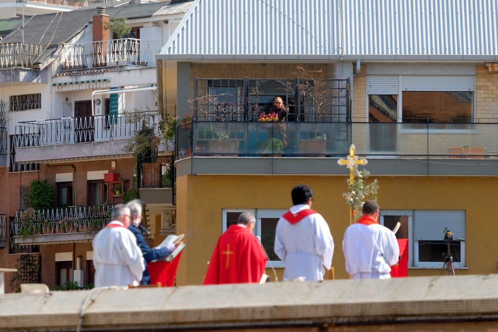 A faithful from a facing balcony follows the celebration of the Palm Sunday Mass on the roof of the church of San Pio X in Rome.