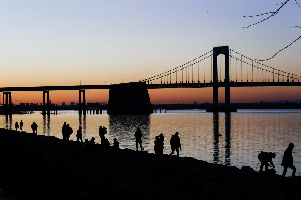 """People gather to watch the sun set behind the Throgs Neck Bridge at LIttle Bay Park on Wednesday in the Queens borough of New York. While New York Gov. Andrew Cuomo said New York could be reaching a """"plateau"""" in hospitalizations, he warned that gains are dependent on people continuing to practice social distancing."""