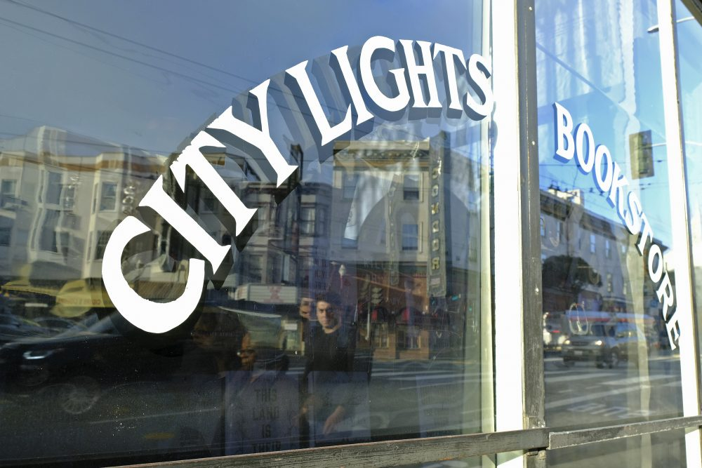 In this March 13, 2020 file photo, people are reflected in the window of the City Lights Bookstore in North Beach as they walk along Columbus Avenue in San Francisco.