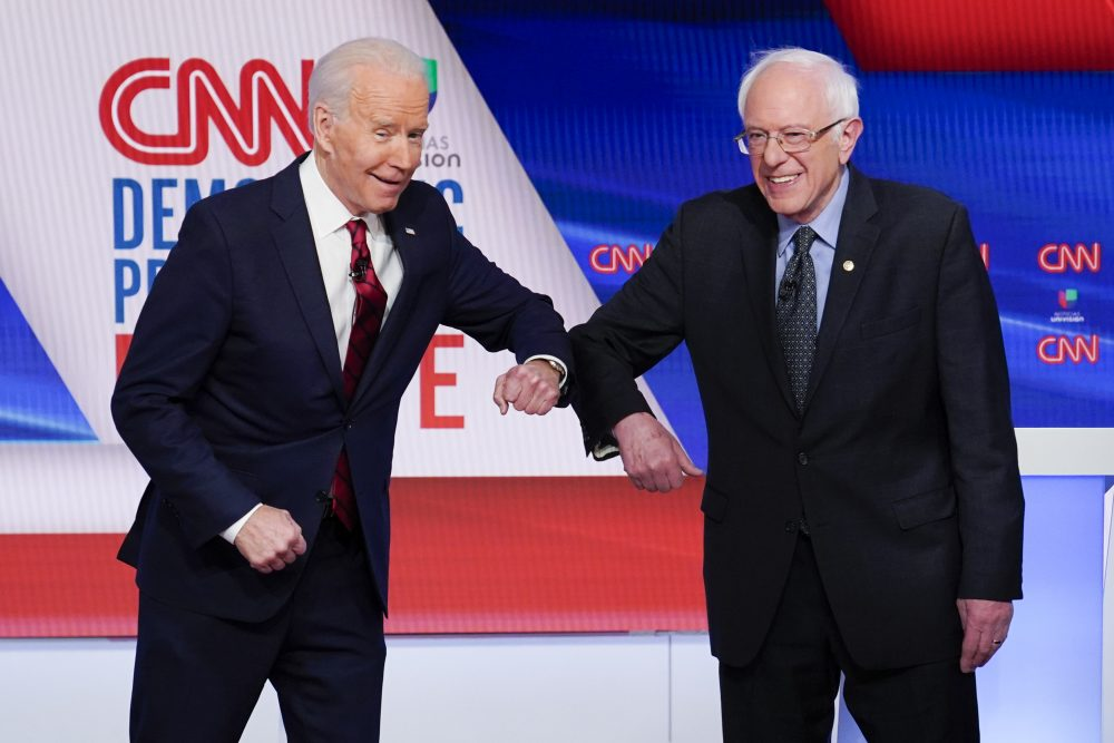 Former Vice President Joe Biden, left, and Sen. Bernie Sanders, I-Vt., right, greet each other before they participate in a Democratic presidential primary debate at CNN Studios in Washington on March 15. Sanders endorsed Biden on Monday.
