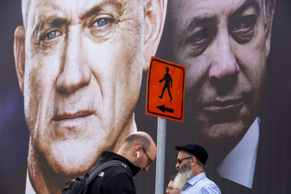 "People walk past an election campaign billboard for the Blue and White party, the opposition party led by Benny Gantz, left, in Ramat Gan, Israel, in February. Prime Minister Benjamin Netanyahu of the Likud party is pictured at right. Netanyahu and Gantz announced Monday, that they have forged a deal to form an ""emergency"" government."