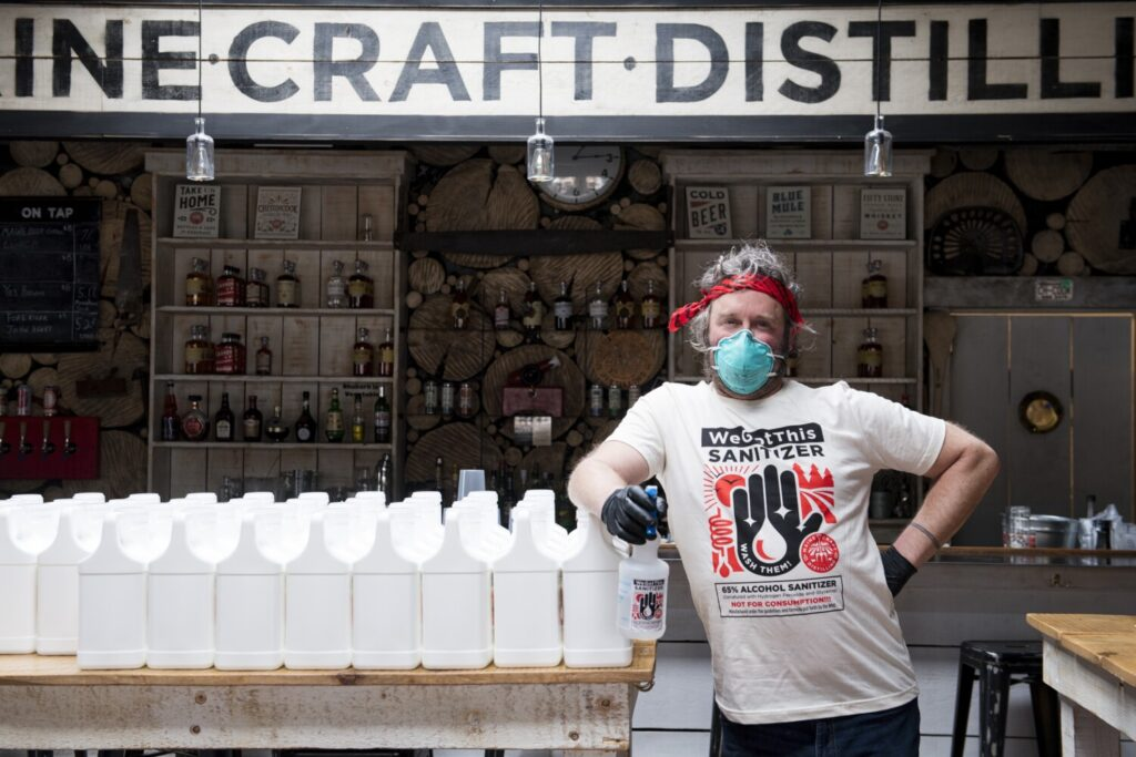 Michael Gatlin, an employee at Maine Craft Distilling in Portland, prepares to distribute more containers of hand sanitizer to those in need.