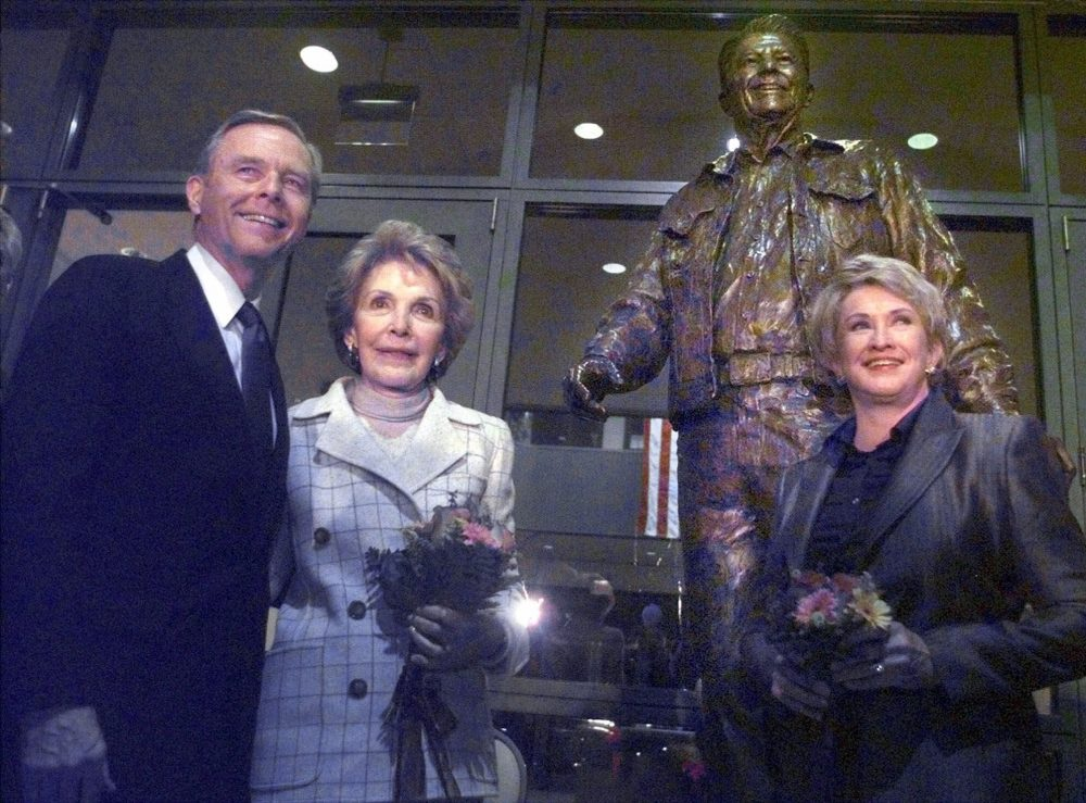 """From left, California Gov. Pete Wilson, Nancy Reagan and sculptor Glenna Goodacre stand in front of """"After the Ride,"""" a bronze sculpture of Ronald Reagan in 1998, in front of the main entrance to the Ronald Reagan Presidential Library in Simi Valley, Calif., after the statue's unveiling."""
