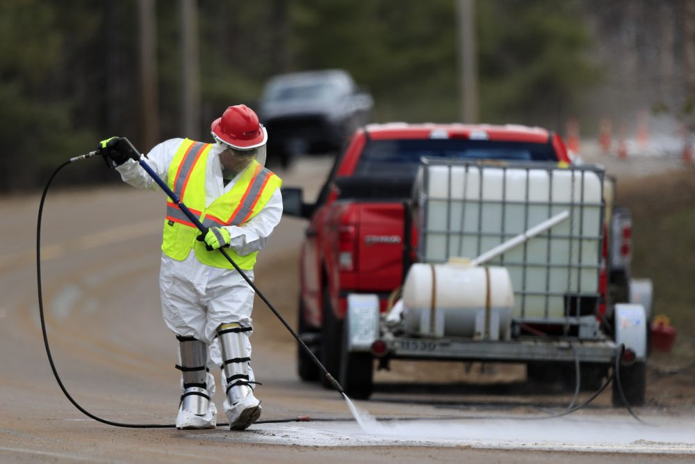 A worker wearing a hazardous material suit hoses debris off a road near the Androscoggin Mill, April 16 in Jay.
