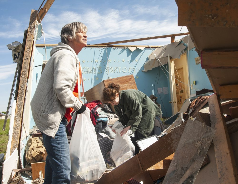 Stephanie Fatheree, right, salvages items from her house damaged from the tornado the previous night with help from a neighbor, on Thursday in Harrisburg, Ark. Fatheree said she took shelter with her mother, Angie, in the bathroom during the tornado.