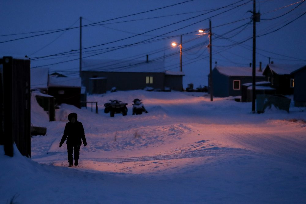 A woman walks before dawn in Toksook Bay, Alaska, a mostly Yuip'ik village on the edge of the Bering Sea, in January. Native American leaders are raising questions about how $8 billion in federal coronavirus relief tagged for tribes will be distributed, with some arguing that for-profit Alaska Native corporations shouldn't get a share of the funding.