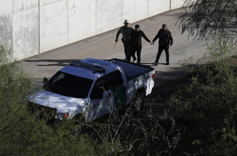 A U.S. Customs and Border Patrol agent walks with suspected immigrants caught entering the country illegally Nov. 16, 2016, along the Rio Grande in Hidalgo, Texas. The Trump administration has quietly shut down the nation's asylum system for the first time in decades amid coronavirus concerns, largely because holding people in custody is considered too dangerous.