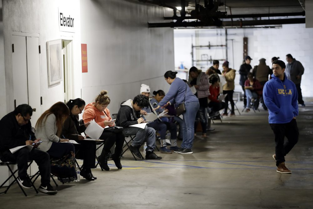 Unionized hospitality workers wait in line in a basement garage to apply for unemployment benefits  in Los Angeles in March.