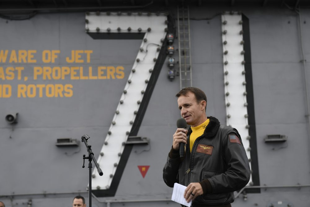 Navy Capt. Brett Crozier, commanding officer of the aircraft carrier USS Theodore Roosevelt, addresses the crew on the ship's flight deck on Nov. 15. U.S. defense leaders are backing the Navy's decision to fire the captain, who sought help for his coronavirus-stricken aircraft carrier. Videos showing his sailors cheering him as he walked off the vessel went viral on social media.