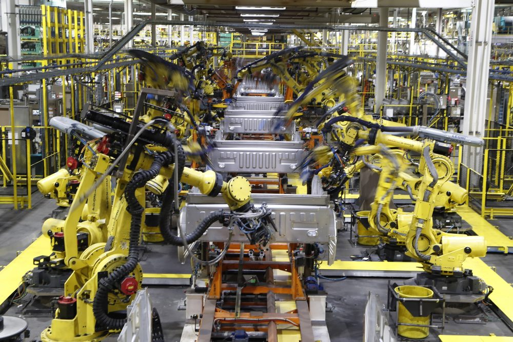 Robots weld the bed of a 2018 Ford F-150 truck on the assembly line at the Ford Rouge assembly plant in Dearborn, Mich. U.S. businesses are edging their way toward figuring out how to bring their employees back to work amid the  pandemic.