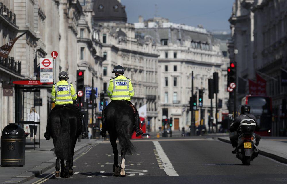 Mounted police officers patrol along a deserted Regent Street in London, as the country is in lockdown to help curb the spread of the coronavirus, Wednesday, April 15.