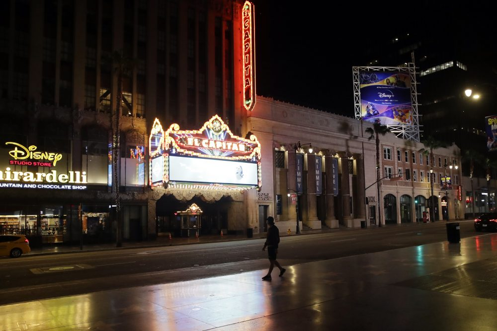 A man walks past El Capitan Theatre along the mostly empty Hollywood Boulevard on Thursday, April 2, 2020, in Los Angeles.